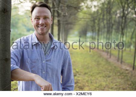 Un homme appuyé contre un arbre regardant la caméra. Banque D'Images
