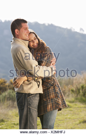 Young couple embracing in rural scene Banque D'Images
