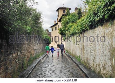 Italie, Toscane, Florence, père de trois enfants (10-11, 12-13) walking on rainy day Banque D'Images