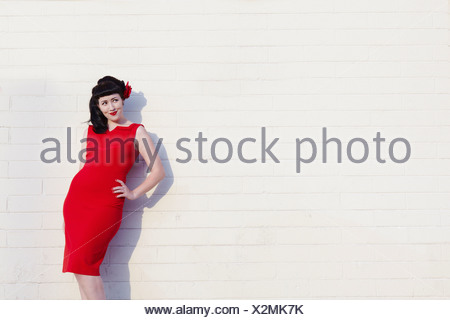 Belle jeune femme en robe rouge leaning on wall Banque D'Images
