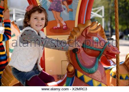 Belle petite fille (4-5) équitation cheval carrousel Banque D'Images