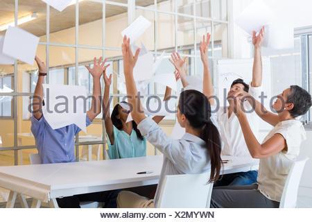 Célébrer les gens d'affaires documents de jeter en l'air Banque D'Images