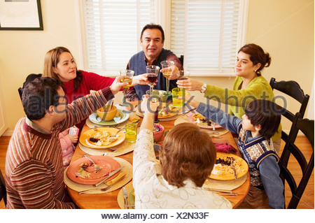 Family toasting each other at dinner table Banque D'Images