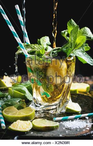 Verre de mojito cocktail Rhum avec bec verseur et le soda, la menthe fraîche, des limes et des cubes de glace sur fond noir. Banque D'Images