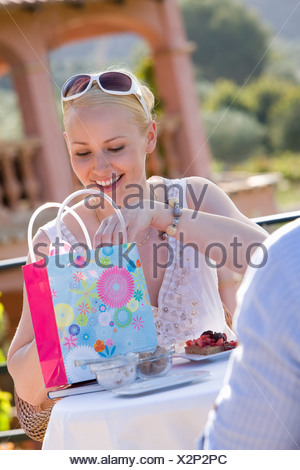 Smiling woman looking in gift bag on cafe patio Banque D'Images