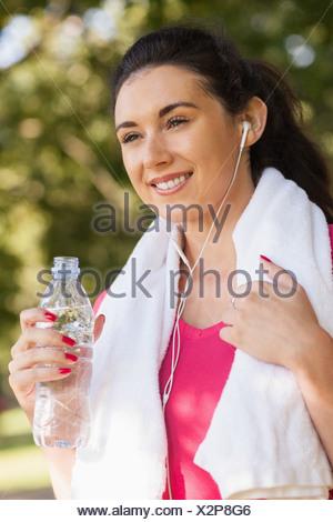 Happy sporty woman wearing sportswear tenant une bouteille