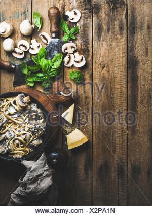 Dîner de style italien. Des pâtes aux champignons crémeux spaghettis dans poêle en fonte avec fromage parmesan, feuilles de basilic frais et de pep Banque D'Images