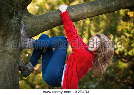 Teenage girl climbing tree in park Banque D'Images