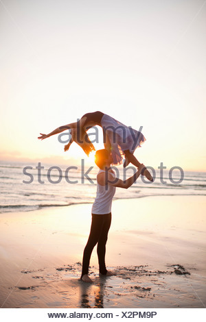 Jeune homme partenaire de danse de levage sur la plage ensoleillée Banque D'Images