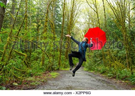 Jumping femme en forêt avec parapluie rouge Banque D'Images