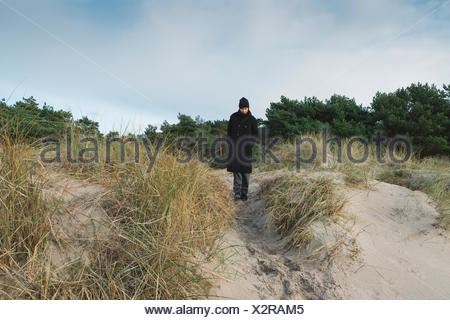 Woman standing on sand dune in Austre, Suède Banque D'Images