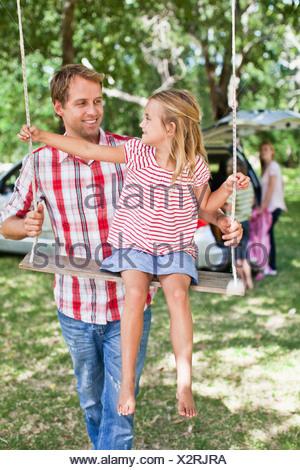 Père fille poussant on swing Banque D'Images