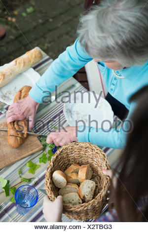 Senior woman cutting bread, high angle Banque D'Images