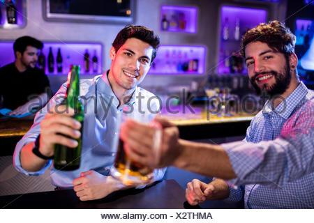 Portrait des hommes montrant verre de bière et une bouteille de bière Banque D'Images