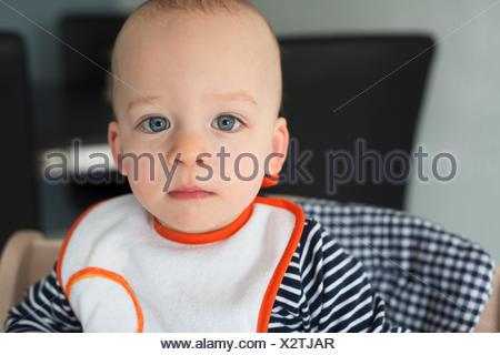 Portrait de bébé garçon regardant dans une chaise haute Banque D'Images