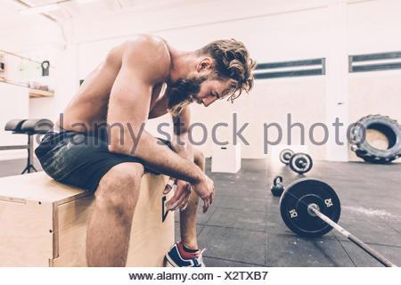 Épuisé homme cross trainer de prendre une pause de la salle de sport en haltérophilie Banque D'Images