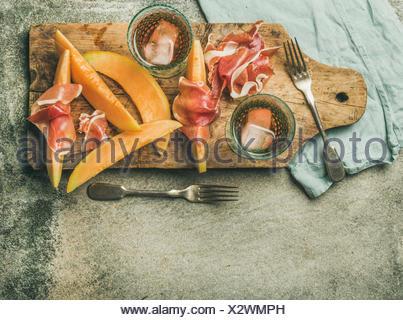 Vin d'été partie. Flatlay de vin snack-jambon prosciutto, melon et verres de vin rose avec de la glace sur planche de bois rustique au béton gris background Banque D'Images