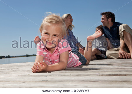 Girl laying on dock avec la famille Banque D'Images