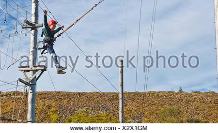 Fille se balançant sur rope swing Banque D'Images