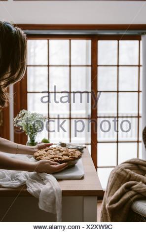 Une femme est photographié alors qu'elle est mise en place une tarte aux pommes du four sur la table. Banque D'Images