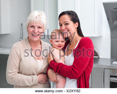 Father mother holding baby in kitchen Banque D'Images