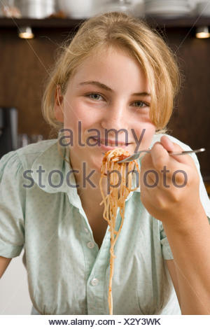 Teenage girl eating spaghetti Banque D'Images