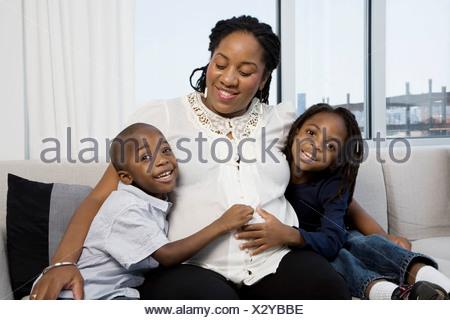 Deux garçons avec leurs mains sur leur ventre de maman enceinte Banque D'Images
