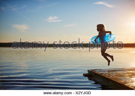 Fille sautant hors d'une jetée Banque D'Images