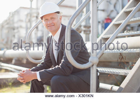 Businessman in hard-hat assis sur mesures industrielles Banque D'Images