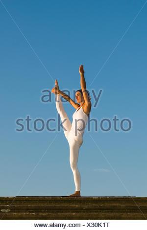 Jeune femme la pratique de l'Hatha Yoga, à l'extérieur, montrant la pose Anjaneyasana, soulevé la main pour poser le pied Banque D'Images