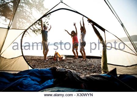Trois jeunes adultes de sourire et de danser autour d'un feu de camp sur une excursion en kayak et camping sur un lac dans l'Idaho. Banque D'Images