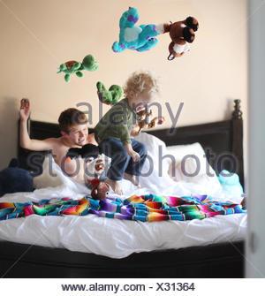Garçon sautant sur lit frères et jetant des jouets mous dans l'air Banque D'Images