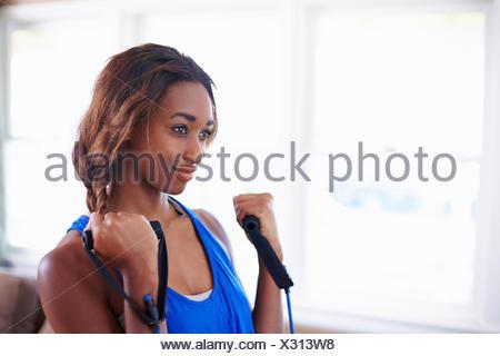 Jeune femme exerçant dans la salle de séjour Banque D'Images