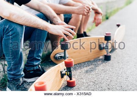 Les jeunes hommes assis avec planches à roulettes Banque D'Images