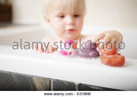 Enfant jouant avec des jouets dans la baignoire Banque D'Images