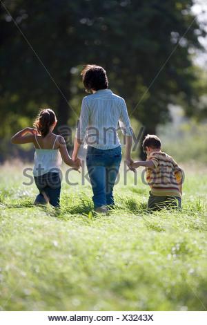 Mère marche main dans la main avec les fils 68 et 79 fille dans le champ Vue arrière Banque D'Images