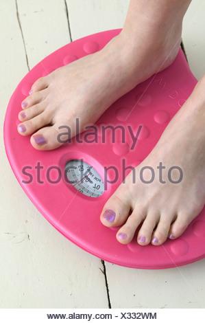 Pieds de femmes cultivées sur rose permanent pèse sur plancher de bois blanc Banque D'Images