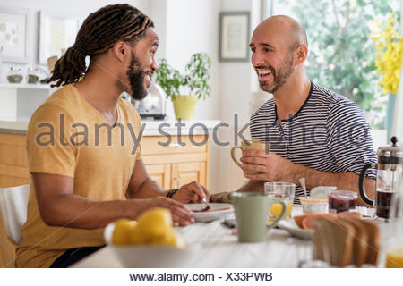 Smiley couple having breakfast in kitchen Banque D'Images