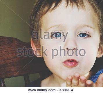 Portrait Of Cute Blue Eyed Boy Blowing A Kiss Banque D'Images
