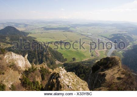 Uitzicht vanaf de Drie Kronen met de rivier Dunajec en op de achtergrond de besneeuwde toppen van de Tatra. Vue depuis les trois couronnes de l'autre côté de la rivière Dunajec avec les pics couverts de neige de la Tatra en arrière-plan. Banque D'Images