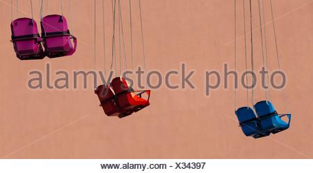 Sièges vides d'un Chairoplane ou carrousel de rotation en avant d'une façade de maison, Berlin, Germany, Europe Banque D'Images