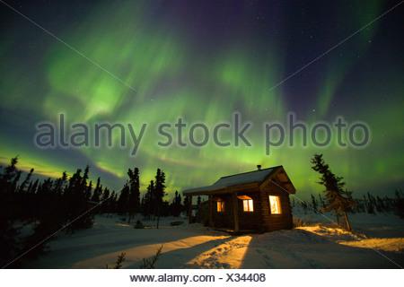 Des rideaux vert et violet aurores boréales) danse sur une cabine chaude dans les collines près de Fairbanks, Alaska Banque D'Images