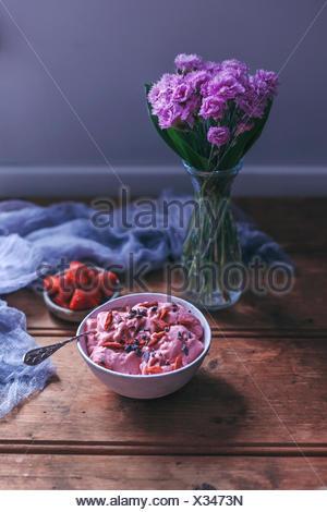 La crème glacée fraise banane dans un bol garni de plumes de cacao et baies de goji