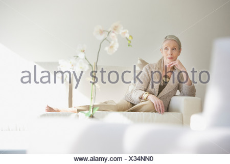 Femme assise sur un canapé dans une pièce blanche Banque D'Images