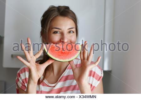 Femme couvrant la bouche avec tranche de pastèque Banque D'Images