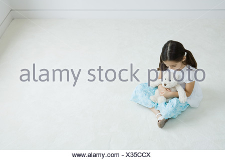 Fille assise sur le terrain teddy bear on lap, high angle view Banque D'Images