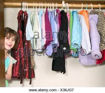 Jeune fille se cachant dans penderie Banque D'Images