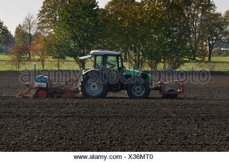 Tracteur avec rouleau avant et une machine de semis à l'arrière sur un champ, Rhénanie du Nord-Westphalie, PublicGround Banque D'Images