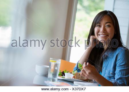 Une femme assise de manger dans un café. Banque D'Images