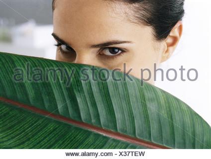 Woman looking at camera, palm leaf couvrant partiellement le visage, close-up Banque D'Images